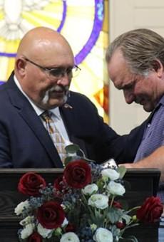 Frank Pomeroy (left) prays with a congregant.