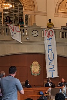 Protestors lower banners during a city council meeting protesting this summer's delay of the paid sick time ordinance.