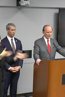Bexar County Judge Nelson Wolff addresses the press while a sign language interpreter translates.