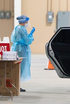 Healthcare workers assist with a drive-through coronavirus test at San Antonio's Freeman Coliseum site.
