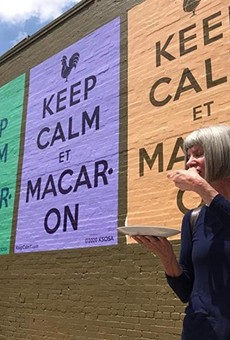 Kathy Sosa eats a macaron in front of the new mural.