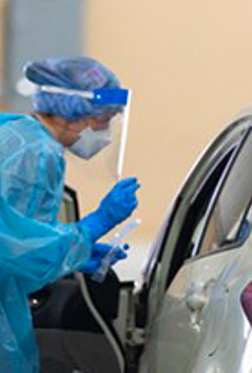 A public health worker prepares to test a person for COVID-19 at a drive-through testing site in San Antonio.
