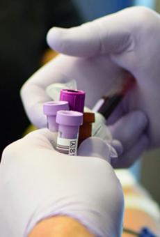 A technician handles vials of blood during a donation drive.