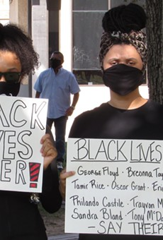 Two protesters hold up signs at a San Antonio march against police brutality.