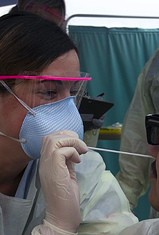 A medical technician swabs a patient at a COVID-19 testing site.
