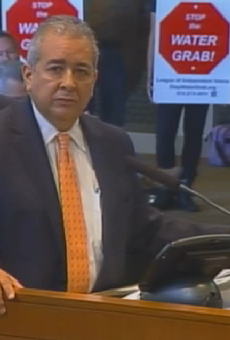 This screengrab shows SAWS CEO Robert Puente answering questions from City Council last October about the Vista Ridge pipeline. Protestors stand behind him.