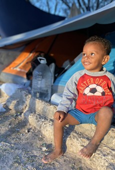 """A child waits in a shelter at a Matamoros border camp. Trump's """"remain in Mexico"""" policy has faced criticism for exposing asylum seekers to violence and unsanitary conditions in encampments along the border."""
