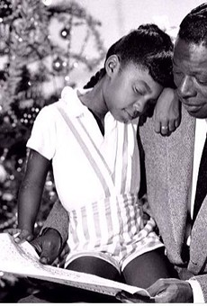 Cole, on the lap of her legendary father, a man she would grow to be considered equal to as a vocalist