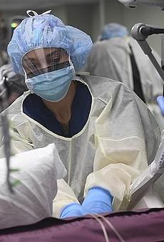 A surgical nurse prepares a COVID-19 patient for a procedure in an intensive care unit.