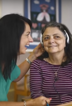 A woman suffering from dementia brightens up while listening to music with her daughter.