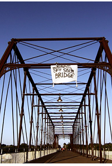 Activists climbed the Hays Street Bridge to hang a banner opposing development after plans for a brewery on public land emerged in 2012.