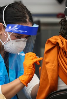 A woman receives her COVID-19 vaccination at the city's Alamodome site.