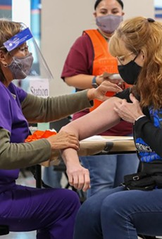 A San Antonio resident receives her shot at the Alamodome mass-vaccination site.