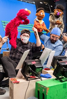Bradley Freeman Jr. (second from right) controls the  Wesley Walker Muppet during a shoot for a Sesame Street online series.