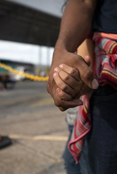A Honduran migrant holds his daughter's hand at an immigration checkpoint in Nuevo Laredo.