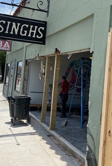 Eric Treviño, a partner in Singhs, watches a work crew clear debris out from the restaurant.