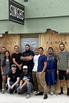 Employees of Singh's Vietnamese pose in front of the restaurant's now boarded-up storefront.