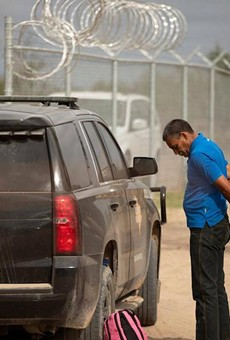 A Texas Department of Public Safety trooper arrests Nerio, a Venezuelan migrant, on private riverside property in Del Rio, just beyond a newly installed fence paid for by the state. Credit: Miguel Gutierrez Jr./The Texas Tribune
