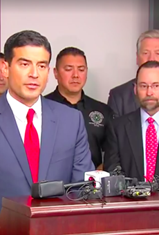 Distract Attorney Nico LaHood addresses reporters on Friday, with a dated photo of Genene Jones behind him.