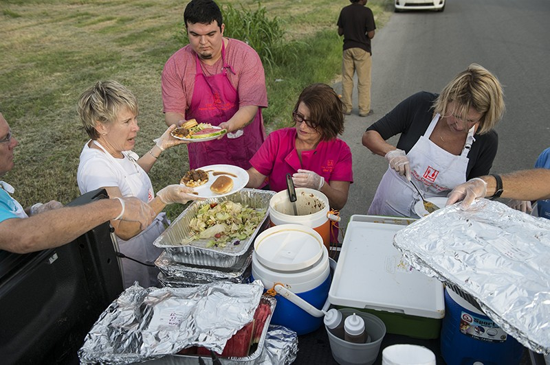 Joan Cheever (center) and her volunteers plate meals on Tuesday, July 7. - CARLOS SANCHEZ