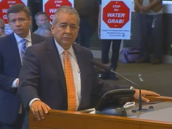 This screengrab shows SAWS CEO Robert Puente answering questions from City Council last October about the Vista Ridge pipeline. Protestors stand behind him. - SAN ANTONIO CURRENT