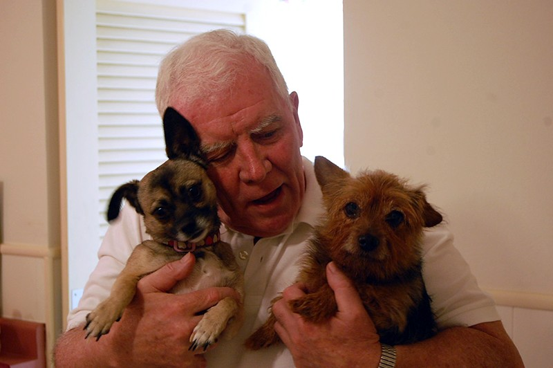 Father Jim Hynes with two of the strays he adopted. - MICHAEL MARKS