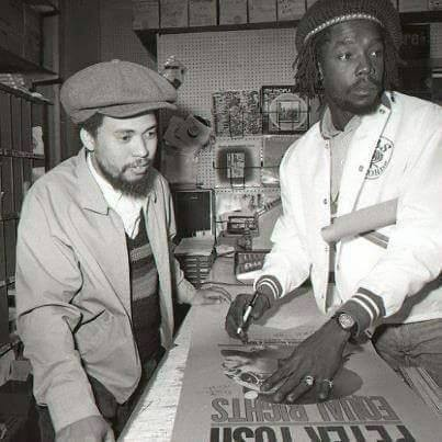Peter Tosh (right) signing a poster for a fan. - FACEBOOK