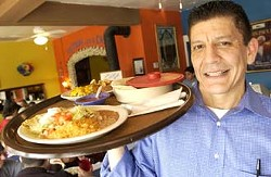 Waiter Ernie Ochoa carries out a plate of enchiladas verdes (front), chilaquiles plate and fresh warm tortillas during a busy Sunday brunch at James' Cafe.