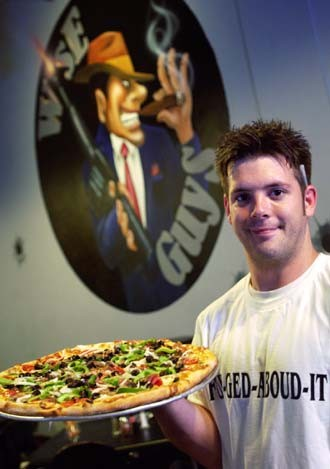 Waiter Will Zebell shows off a Supreme Pizza recently at Wise Guys Bar & Pizzeria. The Supreme pie features a homemade crust topped with tomato sauce, fresh onion, bell pepper, olives, mushrooms, pepperoni, canadian bacon, sausage, and meatball.