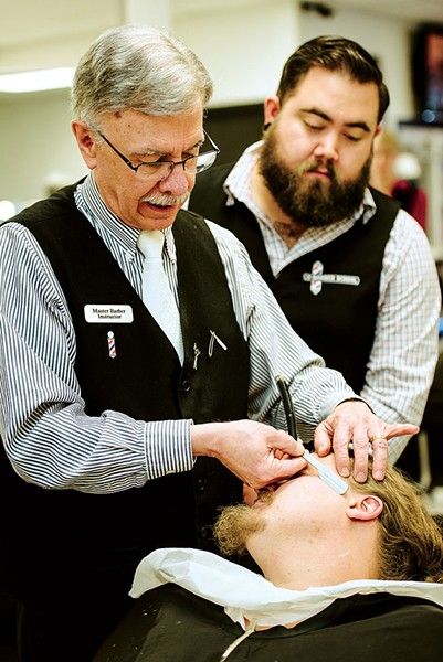 Milton Larsen, master barber instructor at The Barber School, demonstrates a straight-razor shave