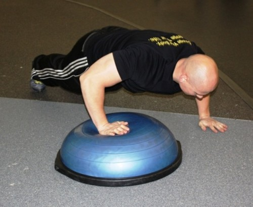 Personal trainer Nick Remy does pushups with one hand on a bosu ball for increased conditioning. - WINA STURGEON