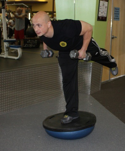 PERSONAL TRAINER NICK REMY USES DUMBBELLS AND A BOSU BALL FOR A CORE-WORKING BALANCE DRILL. - BY WINA STURGEON