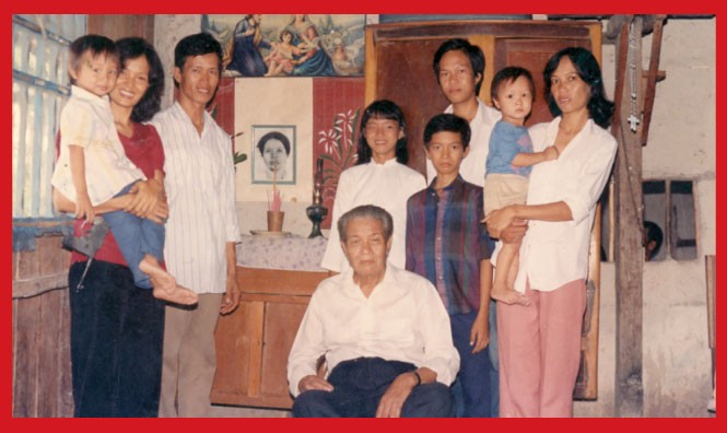 Tam as a child, at left, with his mother & father and the rest of his - family in their home in a village south of Saigon.