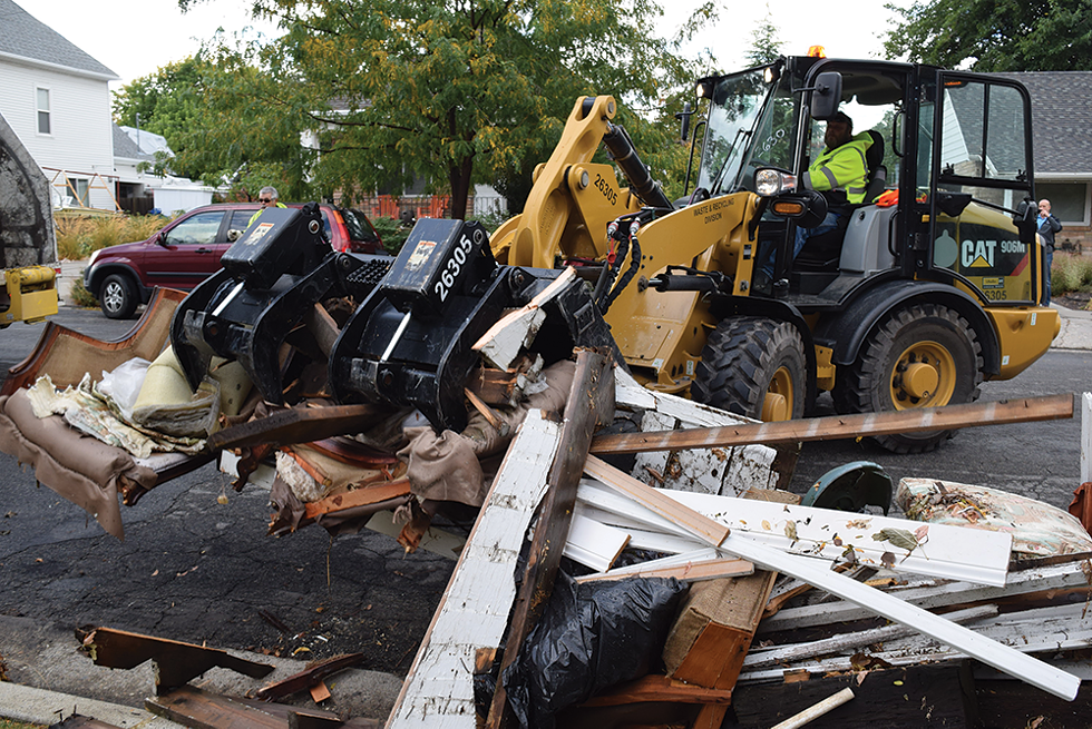 Workers with the city's Call 2 Haul program collect the junk outside Farrina Coulam's East Liberty Park home. - RAY HOWZE
