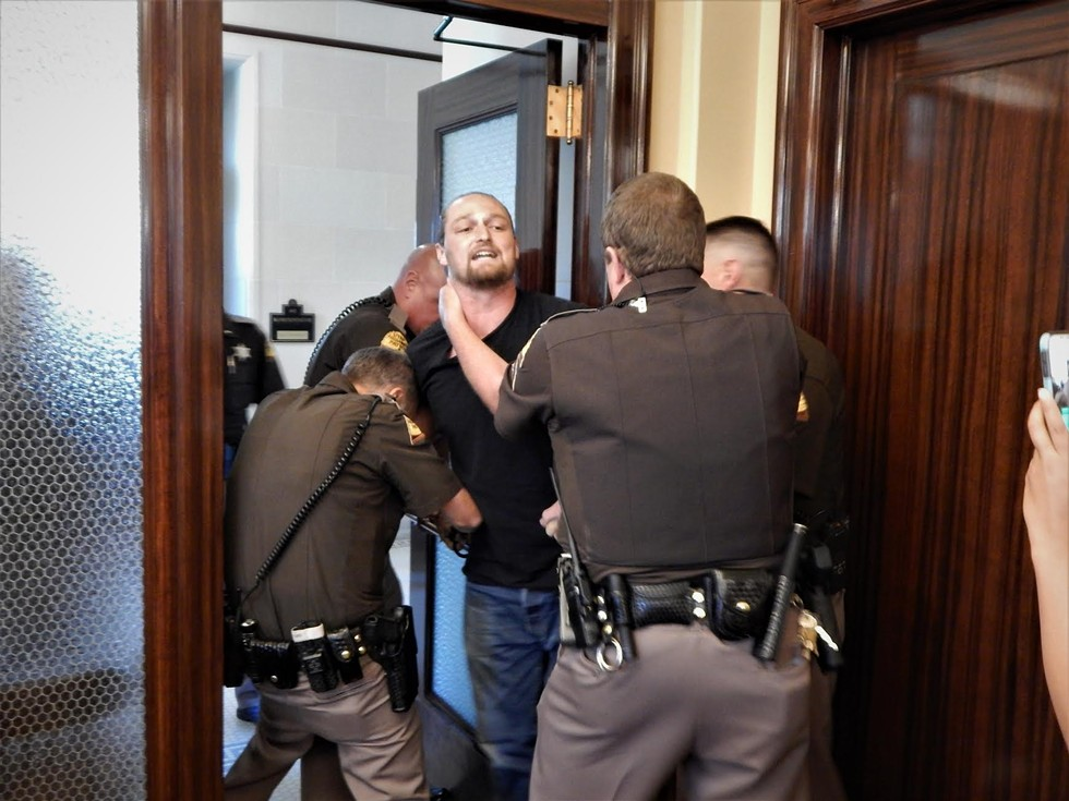 Ethan Petersen being hauled away by state troopers. - PETER HOLSLIN