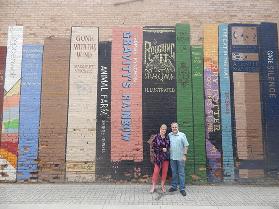 Cindy and Bret Eborn, the couple behind iconic downtown bookshop Eborn Books, pose in front of the mural located on the side of their now-shuttered shop. - PETER HOLSLIN