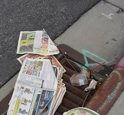 Copies of City Weekly thrown in a downtown gutter - LARRY CARTER