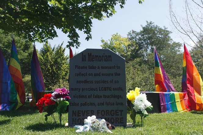 A mock tombstone was erected on Saturday to mark LDS LGBTQ lives lost. - JORDAN FLOYD