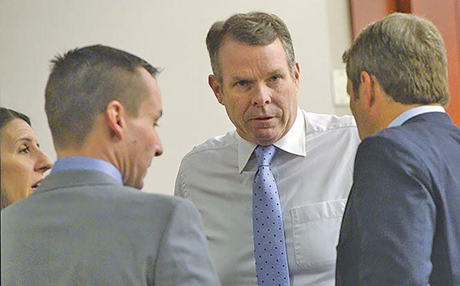 Cara Tangaro (left), Brad Anderson (center) and Scott Williams (right) surround their client, John Swallow, on Wednesday, Feb. 15. - AL HARTMANN/COURT POOL