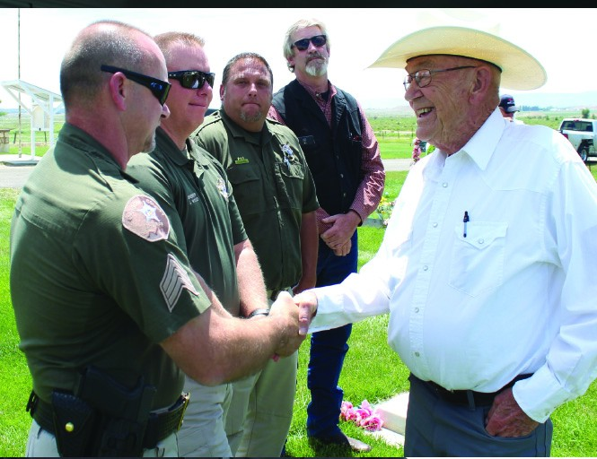 Carbon County Sheriff's Detective David Brewer shakes hands with Duane Jones, Loretta's brother, at the Elmo Cemetery on the day her body was reinterred. On the night of the crime, Duane and his father were across the street from the house in which the murder took place. Also in the photo are Carbon County Sheriff Jeff Wood, Chief Deputy Cletis Steele and Detective Wally Hendricks.