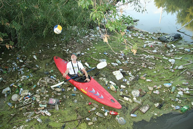 Ray Wheeler, surrounded by garbage, floats in his kayak down the Jordan River. - AMY O'CONNOR