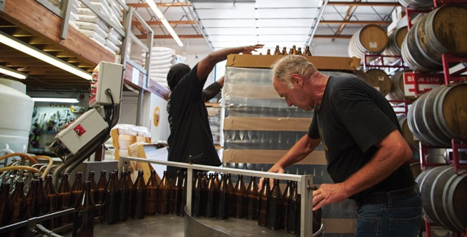 11. Greg Giles and Haley work the bottling process.