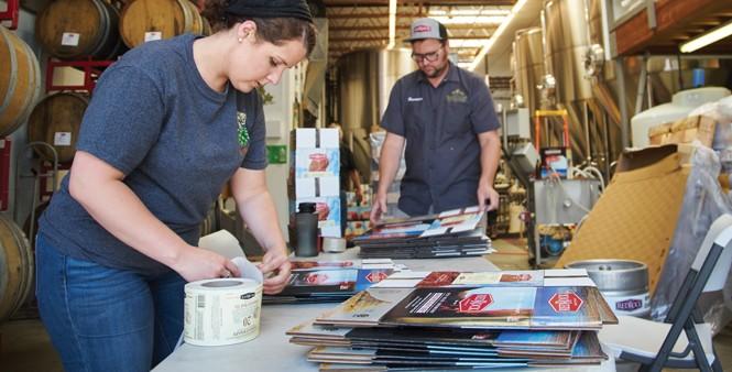 15. Alisha Telles and Brandon Smith assemble and label boxes.