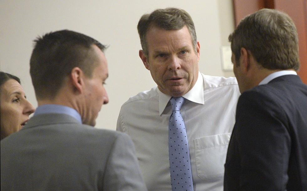 Cara Tangaro (left), Brad Anderson (center) and Scott Williams (right) surround their client, John Swallow, on Wednesday, Feb. 15. - AL HARTMANN/POOL