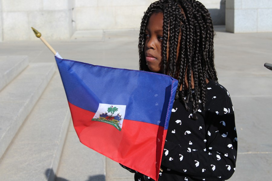 A little girl waves the flag of Haiti during SLC's Rally Against Racism. - ENRIQUE LIMÓN