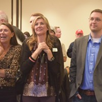 Christine Stenquist, middle, stands with her mom, Kathy Marriott, and TRUCE policy director, Thomas Paskett, during Tuesday's Prop 2 election watch party at the University Park Marriott Hotel.