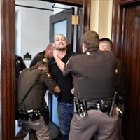 Ethan Petersen being hauled away by state troopers.
