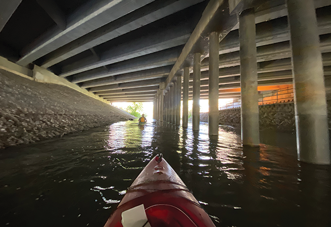 Kayakers pass under Interstate 215 on the Jordan River between Murray and Taylorsville. - BENJAMIN WOOD