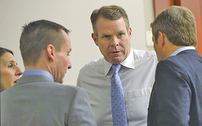 Cara Tangaro (left), Brad Anderson (center) and Scott Williams (right) surround their client, John Swallow, on Wednesday, Feb. 15. - AL HARTMANN/COURT POOL