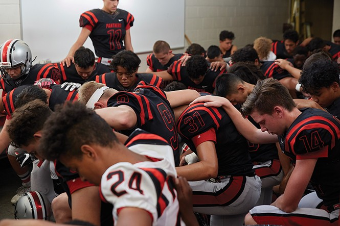 The Panthers huddle in prayer last Friday evening before the season opener. - STEPHEN VARGO